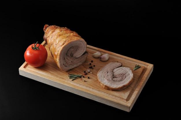 Fleischstück auf einem hölzernen brett auf schwarzer oberfläche.