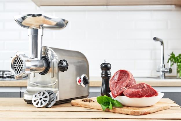 Fleischwolf mit frischem fleisch auf holztisch im kücheninneren