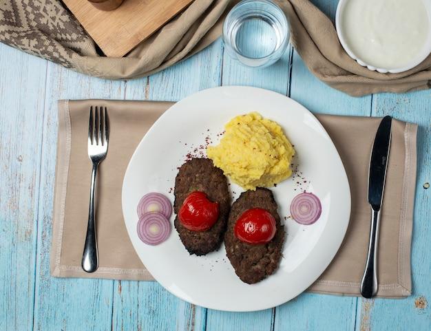 Fleischwürfel mit gegrillter tomate und kartoffelpüree