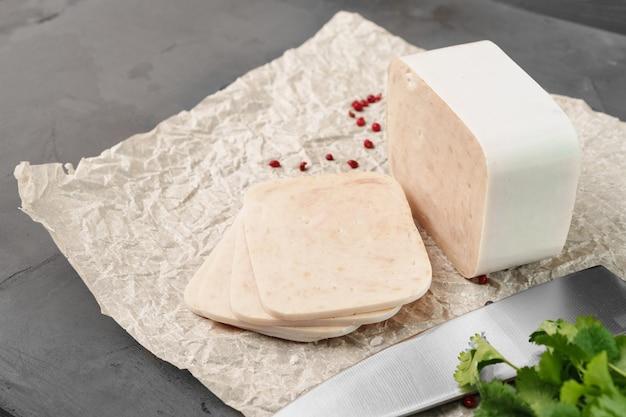 Fleischwurst auf pergament auf grauem hintergrund schließen