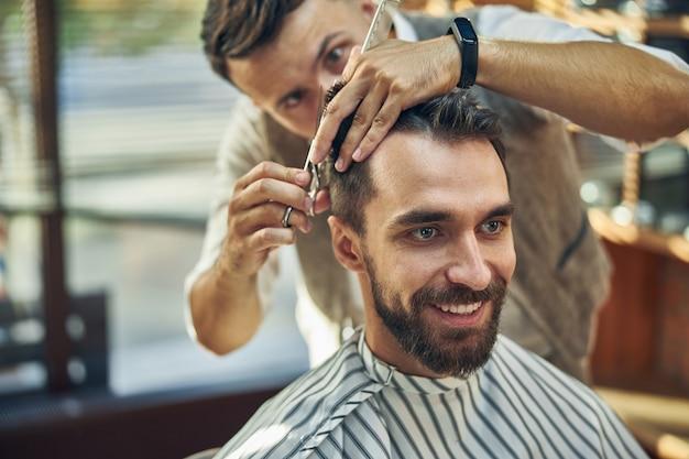Fleißig arbeitender professioneller friseur, der konzentriert aussieht, während er eine schere hält und seinem kunden einen frischen haarschnitt gibt