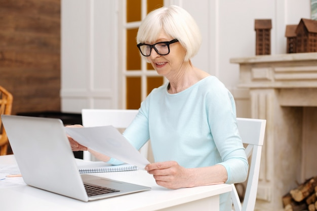 Fleißige aktive ältere frau, die das projekt von zu hause aus verwaltet, während sie einen laptop verwendet, um mit ihren kollegen in kontakt zu bleiben