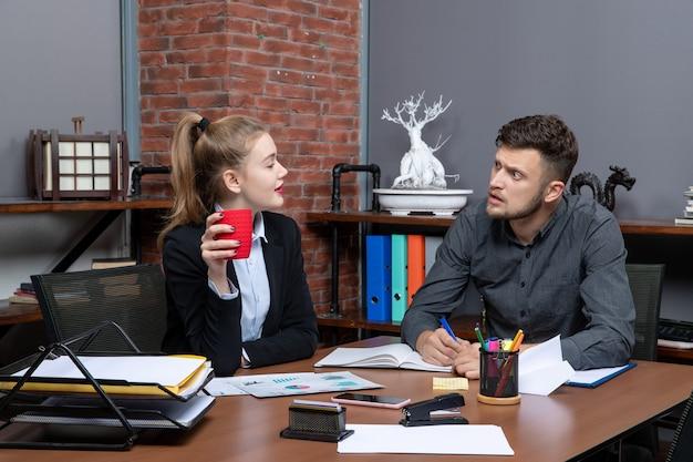 Fleißige facharbeiter diskutieren ein thema in den dokumenten im büro