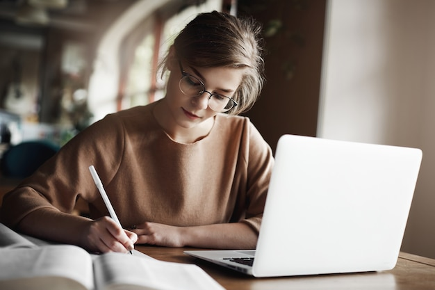 Fleißige frau in trendigen gläsern, die sich darauf konzentriert, einen aufsatz zu schreiben, in einem gemütlichen café in der nähe eines laptops zu sitzen, zu arbeiten und sorgfältig notizen zu machen.