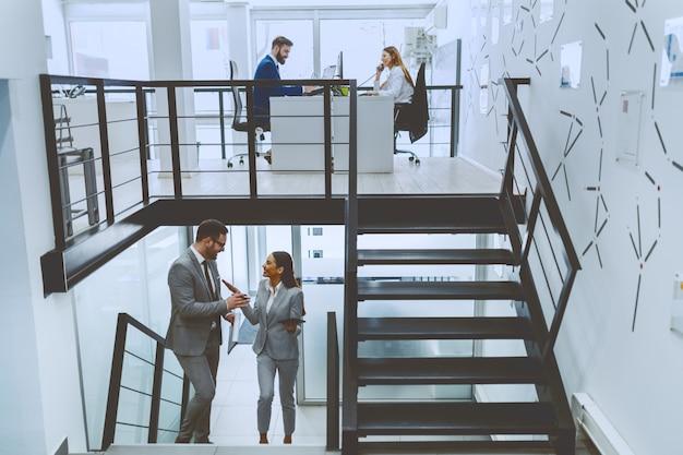 Fleißige mitarbeiter in der firma. zwei von ihnen sitzen am tisch und arbeiten, während die anderen zwei die treppe hinaufsteigen und reden.