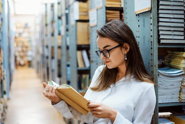 Fleißige studentin in einer weißen bluse und brille, die ein buch in der bibliothek liest