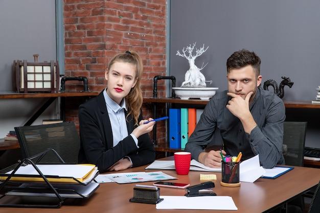 Fleißige und beschäftigte facharbeiter diskutieren ein thema in den dokumenten im büro