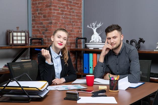 Fleißige und positive facharbeiter diskutieren ein thema in den dokumenten im büro