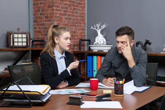 Fleißige und verwirrte facharbeiter diskutieren ein thema in den dokumenten im büro