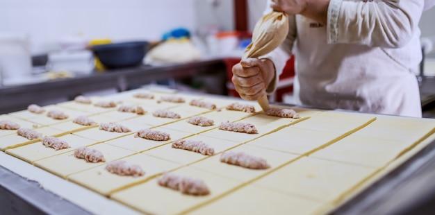 Fleißiger bäcker, der gebäck mit köstlichem pudding füllt. bäckerei interieur.