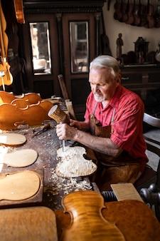 Fleißiger leitender schreiner, der an seinem kreativen projekt in der tischlerei arbeitet