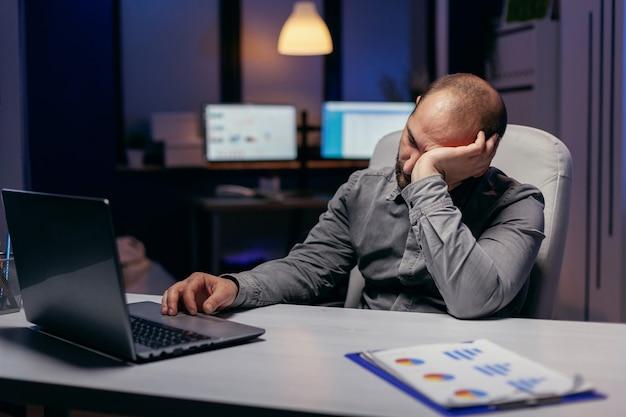 Fleißiger manager, der am arbeitsplatz mit der hand auf der laptoptastatur ein nickerchen macht workaholic-mitarbeiter schläft ein, weil er spät nachts allein im büro für ein wichtiges unternehmensprojekt arbeitet.