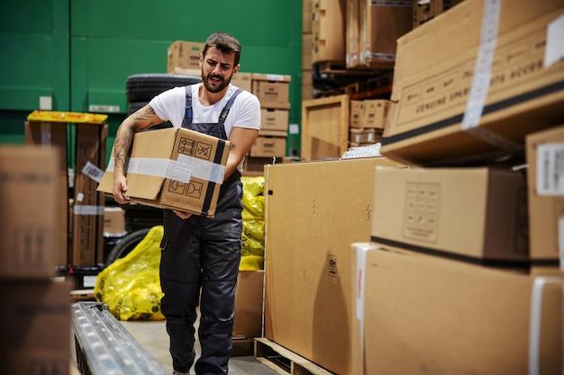 Fleißiger tätowierter bärtiger arbeiter, der durch das lager geht und eine sehr schwere große kiste trägt, die für den export bereit ist.
