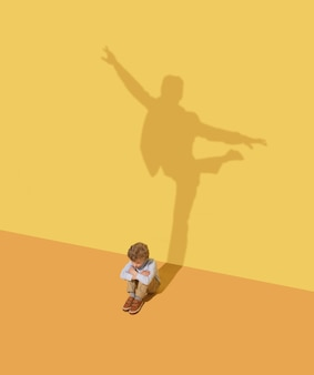 Flexibilität. kindheits- und traumkonzept. konzeptbild mit kind und schatten auf der gelben studiowand. kleiner junge will balletttänzer, theaterkünstler oder geschäftsmann, büromann werden.