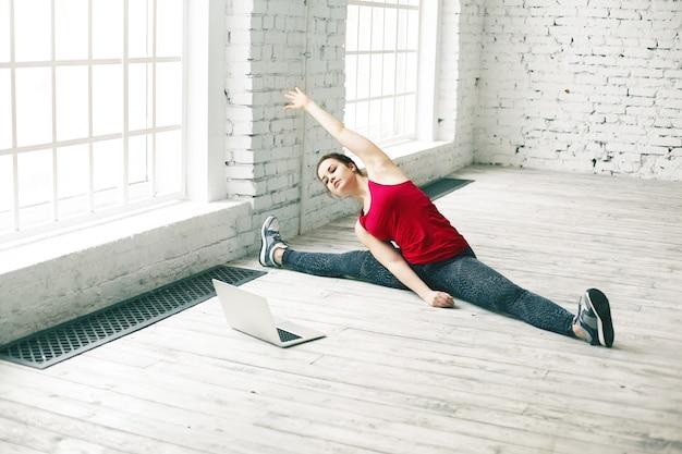 Flexibilität und stärke. wunderschöne junge frau mit perfektem körper, der muskeln zu hause streckt, seitenbein spaltet und sich nach rechts biegt, während yoga-tutorial online auf tragbarem computer anschaut