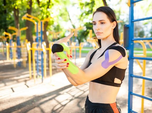 Flexible atemberaubende muskulöse brünette frau mit schwarzem sport-outfit, arm streckend. junge selbstbewusste sportlerin praktiziert gymnastik, aufwärmen, buntes kinesiotaping am körper.