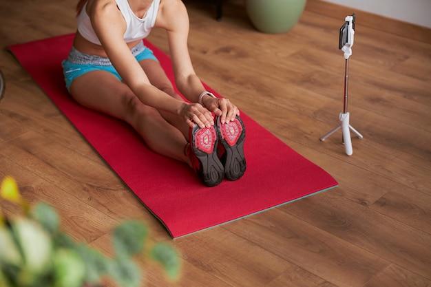 Flexible dame dreht neues video mit vorwärtsbeuge, während sie auf dem boden sitzt