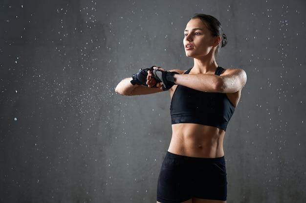 Flexible fitnessfrau, die den arm vor dem training streckt