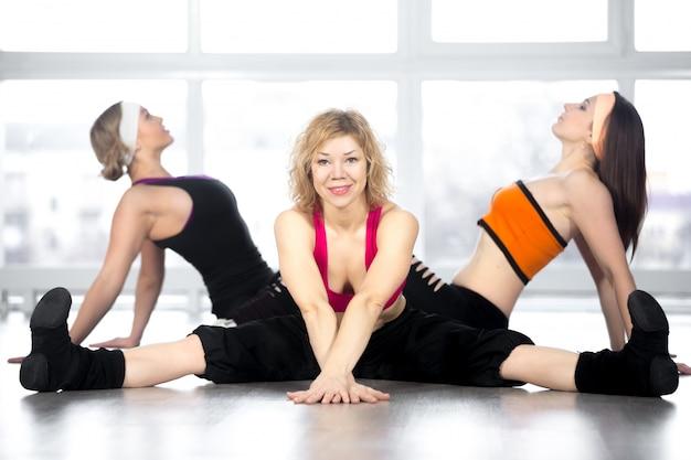 Flexible frau auf dem boden sitzend mit teamkollegen hintergrund