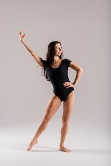 Flexible frau, balletttänzerin in schwarzen bodys, ballerina