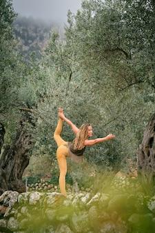 Flexible frau beim yoga in natarajasana im park