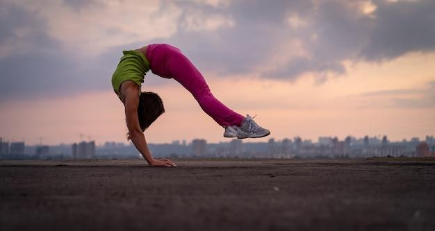 Flexible frau, die handstand im freien auf dem dramatischen sonnenuntergangshintergrundkonzept von yoga und gesundheit macht