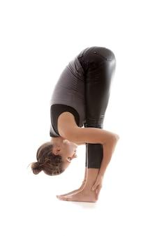 Flexible frau, die ihre knöchel mit den händen zu berühren