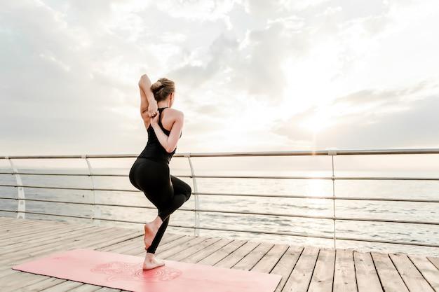 Flexible frau, die morgens yoga asana nahe dem meer auf sonnenaufgang tut