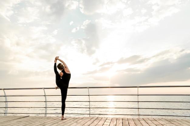Flexible frau, die morgens yoga asana nahe dem meer auf sonnenaufgang, übende sport- und eignungsübungen tut