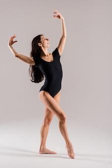 Flexible frau in einem schwarzen body, balletttänzerin, weiße studioaufnahme