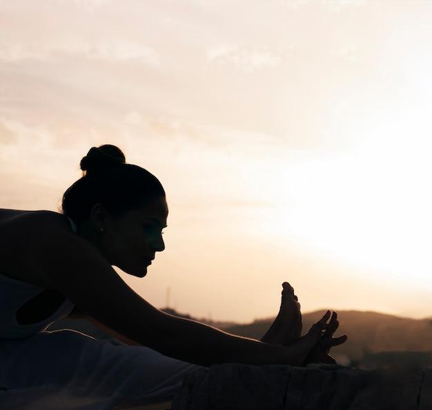 Flexible frau macht yoga im schatten