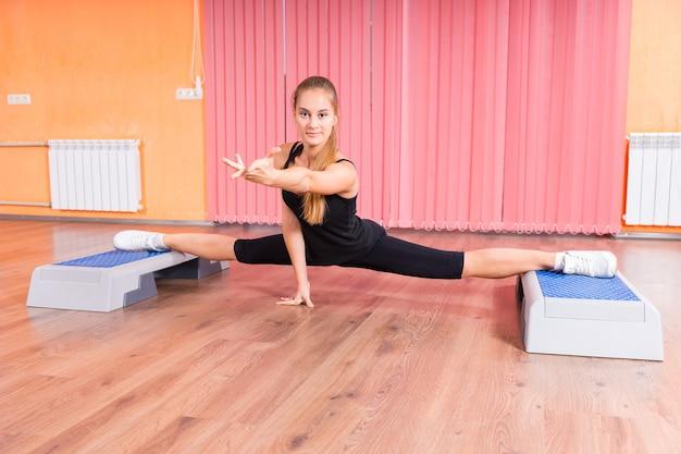 Flexible junge frau spaltet ihre beine in der luft mit zwei fitnessplattformen, streckt eine hand aus und zeigt nach vorne.