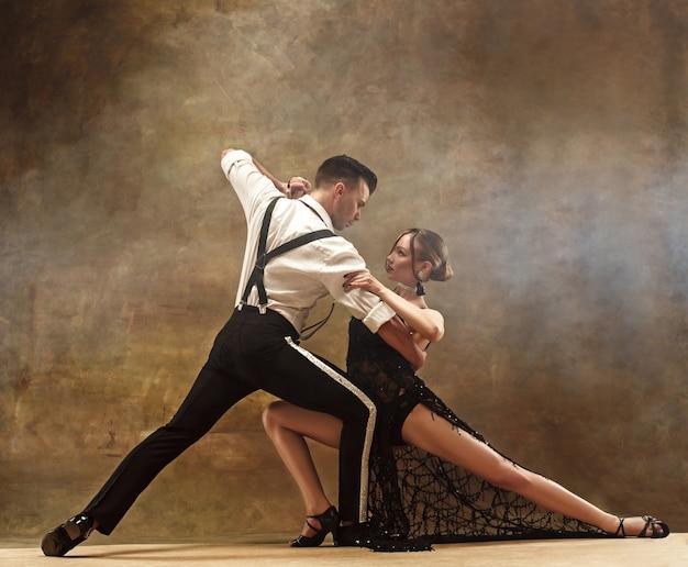 Flexible junge moderne paare tanzen tango im studio. modeporträt von attraktiven tanzpaaren. mann und frau. hingabe. liebe. perfektes hautgesicht und make-up. menschliche emotionen - liebe und leidenschaft