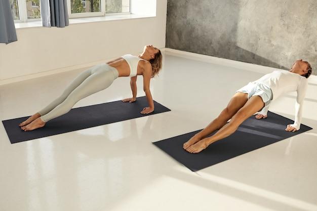 Flexible muskulöse athleten, die sportkleidung tragen, die rückwärts planke auf matten im fitnessstudio tut. barfuß mann und frau machen yoga asanas, um arme und rumpf zu stärken. fitness, ausdauer und entschlossenheit