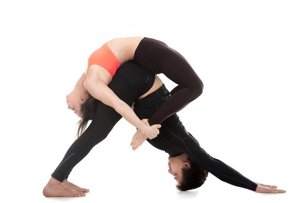 Flexible paare, die eine yoga-haltung zeigt