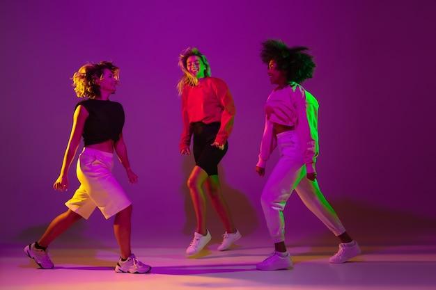 Flexible sportliche mädchen tanzen hiphop in stylischer kleidung auf lilarosa hintergrund beim tanzen