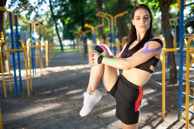 Flexible wunderschöne muskulöse frau mit schwarzem sportoutfit, bein streckend. junge selbstbewusste brünette sportlerin praktiziert gymnastik, aufwärmen, buntes kinesiotaping am körper.