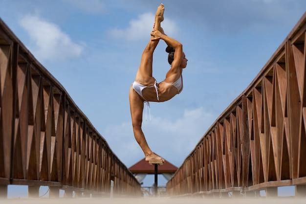 Flexible zirkusartistin hält das gleichgewicht im split auf der brücke gesunder lebensstil yoga lifestyle