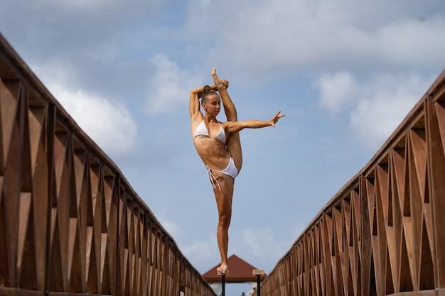 Flexible zirkusartistin hält das gleichgewicht im split auf der brücke. motivation, leidenschaft und leistungskonzept.