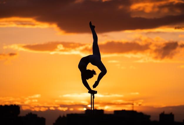 Flexible zirkuskünstlerin hält das gleichgewicht und macht verrenkungen auf dem dach gegen den dramatischen sonnenuntergang und das stadtbild. handstand und gleichgewichtskonzept.