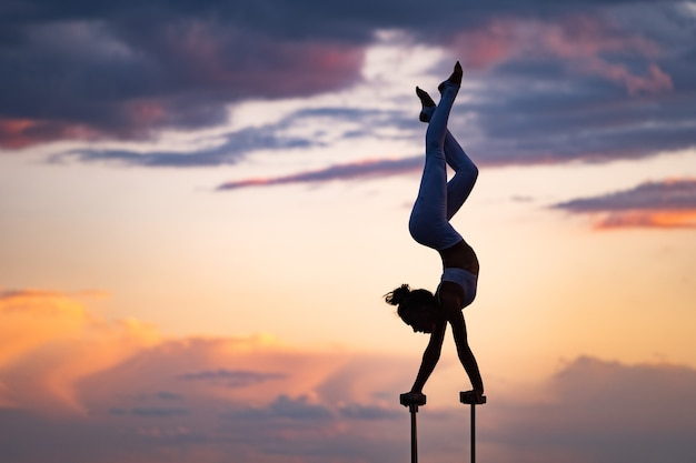 Flexible zirkuskünstlerin hält das gleichgewicht und macht verrenkungen auf dem dach gegen den dramatischen sonnenuntergang und das stadtbild. motivation, leidenschaft und leistungskonzept.