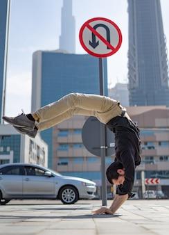 Flexibler acrobat hält das gleichgewicht in den händen mit verschwommenem stadtbild von dubai und verkehrszeichen u-turn ist verboten