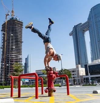 Flexibler acrobat hält mit einer hand das gleichgewicht auf dem feuerwehrhydranten mit dem verschwommenen stadtbild von dubai