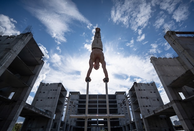 Flexibler männlicher zirkuskünstler, der handstand gegen erstaunliche wolkenlandschaft und moderne konstruktionen macht. symmetrie, balance und kreativitätskonzept.