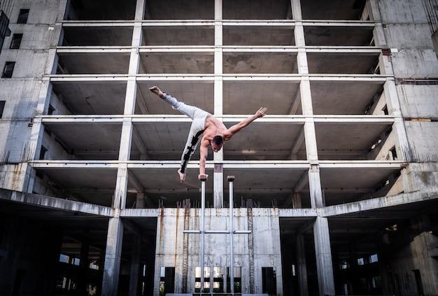 Flexibler männlicher zirkuskünstler halten mit einer hand das gleichgewicht in der betonkonstruktion. individualität, herausragend und originalität.