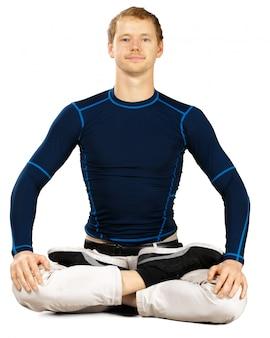 Flexibler sportlicher junger mann, der die übungen ausdehnend lokalisiert auf weißem hintergrund tut