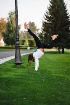Flexibler turner. attraktive dünne frau, die einen backbend macht, während sie einen salto zeigt. draußen