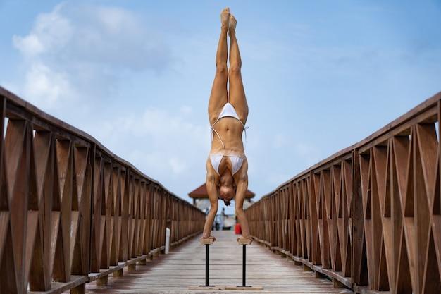 Flexibler weiblicher zirkus, der handstand auf dem pier mit himmelshintergrundreisen kopfüber macht