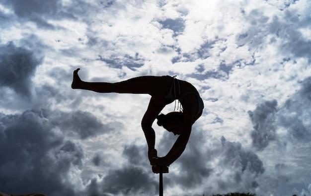 Flexibler weiblicher zirkuskünstler hält das gleichgewicht auf den händen gegen die erstaunliche wolkenlandschaft. individualität, herausragend und originalität.