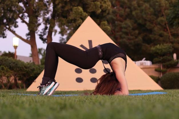Flexibles junges mädchen auf dem gras macht eine brückenpose flexibilität sport yoga gesundheit